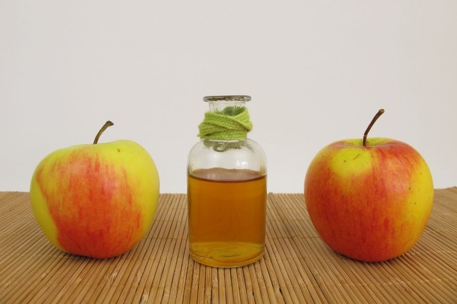 Bottle of apple cider vinegar placed between two apples on a wooden surface
