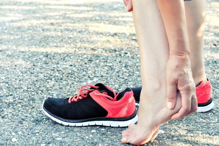 Runner holding painful heel after running on a hard surface