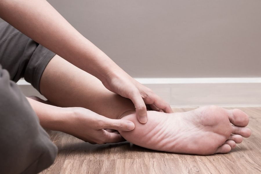 Woman with heel spurs touching the bottom of her heel with her thumbs